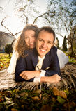 Portrait of happy bride and groom embracing on grass at park Stock Photography