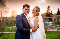 Portrait of happy bride and groom hugging at sunset in park Royalty Free Stock Photos