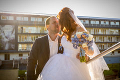 Portrait of happy bride and groom kissing on street at sunny day Stock Photo