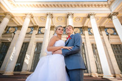 Portrait of happy bride and groom posing against classic buildin Royalty Free Stock Image