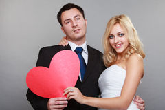 Portrait of happy bride and groom with red heart on gray. Wedding day. Happy blonde bride and groom holding red heart symbol gray background Stock Photos