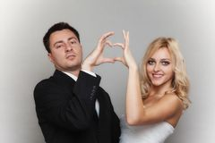 Portrait of happy bride and groom showing heart sign Royalty Free Stock Photography