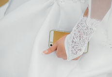 Portrait of happy bride holding gold cell phone Stock Photo
