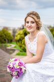 Portrait of happy bride posing at park with bouquet Stock Image
