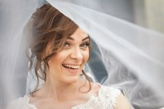 Portrait of happy bride with white veil over her face. Pretty, young bride laughting with white veil over her face. Concept of young gorgeous bride Royalty Free Stock Photo