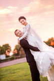 Portrait of happy bridegroom carrying bride on field during sunset Stock Photography