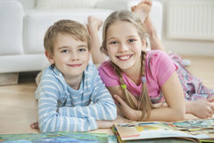 Portrait of happy brother and sister with story books while lying on floor Stock Image