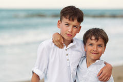 Portrait of happy brothers in white shirts on background of sea Stock Photo