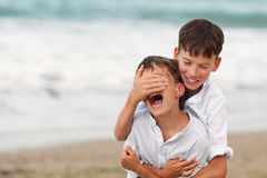 Portrait of happy brothers in white shirts on background of sea Royalty Free Stock Photo