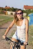Portrait of a happy brunette girl riding bicycle on the clay run Royalty Free Stock Image