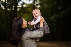 Portrait of happy brunette mother playing with a cute baby daughter. Portrait of happy brunette mother playing and having fun with a cute baby daughter in the Stock Photos