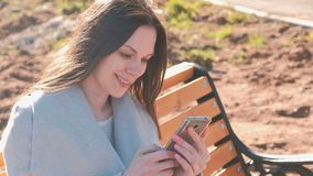 Portrait of happy brunette reading and typing a message in her phone sitting on the bench in park. Portrait of happy brunette reading and typing a message in stock footage