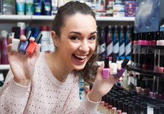 Portrait of happy brunette selecting nail polish Royalty Free Stock Images