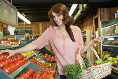 Portrait of a happy brunette shopping for tomatoes in supermarket Stock Image