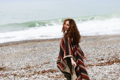 Portrait of happy brunette woman on the beach wearing poncho. Portrait of happy brunette woman by seaside wearing striped red black and beige poncho Stock Photos
