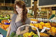 Portrait of a happy brunette woman standing with basket in fruit market Royalty Free Stock Images