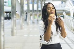Portrait of happy business black woman eats on hold fast food Stock Photos