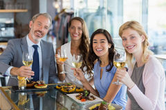 Portrait of happy business colleagues holding beer glasses while having lunch Stock Images
