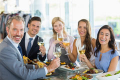 Portrait of happy business colleagues toasting beer glasses while having lunch Stock Image
