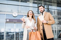 Business couple portrait near the airport. Portrait of a happy business couple in coats stading with tickets and toy airplane in front of the airport entrance Royalty Free Stock Photography