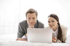 Portrait of happy business couple with laptop in hotel Royalty Free Stock Photos