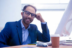 Portrait of happy business leaning on desk Royalty Free Stock Photo