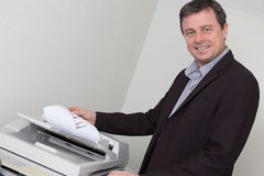 Portrait of a happy business man using machine Stock Images