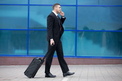 Portrait of happy business man walking with suitcase in a trip. Royalty Free Stock Photo