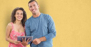 Portrait of happy business people with digital tablet against yellow background Stock Image