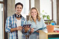 Portrait of happy business people holding digital tablet in creative office Stock Photos