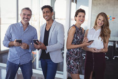 Portrait of happy business people holding mobile phones at office Royalty Free Stock Image