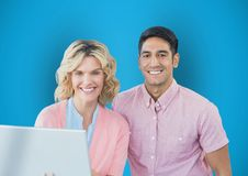 Portrait of happy business people with laptop against blue background. Digital composite of Portrait of happy business people with laptop against blue background Royalty Free Stock Photography
