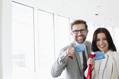 Portrait of happy business people showing identity cards in convention center.  stock photography