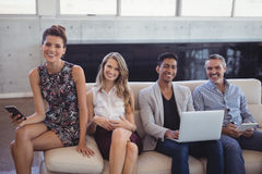 Portrait of happy business people sitting together on sofa while holding technologies Royalty Free Stock Images