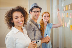 Portrait of happy business people standing by glass wall Royalty Free Stock Photo