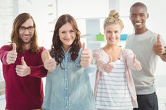 Portrait of happy business team with thumbs up Stock Images