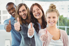 Portrait of happy business team with thumbs up while standing in row Stock Photos
