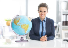 Portrait of happy business woman near earth globe. In office stock photos