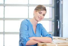 Portrait of a happy business woman relaxing by boxes Stock Image