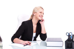 Portrait of happy business woman sitting on her desk. Royalty Free Stock Photo