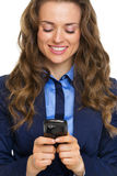 Portrait of happy business woman writing sms Stock Photo