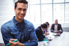 Portrait of happy businessman against as colleagues in meeting room Royalty Free Stock Photo
