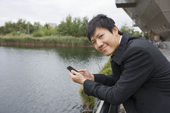 Portrait of happy businessman with cell phone leaning on bridge railing Stock Photography
