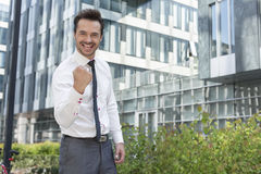 Portrait of happy businessman with clenched fist standing outside office building Stock Image
