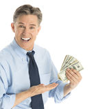 Portrait Of Happy Businessman Gesturing At Dollar Bills. Portrait of happy mature businessman gesturing at dollar bills while standing against white background Royalty Free Stock Photo