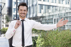 Portrait of happy businessman gesturing while standing outside office building Stock Photos