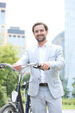 Portrait of happy businessman holding bicycle outdoors Stock Images
