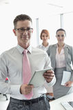 Portrait of happy businessman holding digital tablet with female colleagues in background at office Stock Images