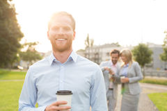 Portrait of happy businessman holding disposable cup with colleagues standing in background Royalty Free Stock Photos