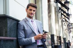 Portrait of a happy businessman holding smartphone Stock Photography